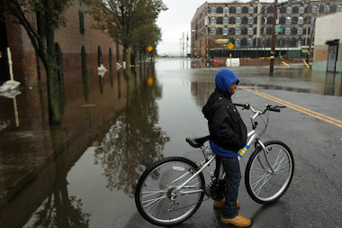 A child stands astride his bicycle on flooded street in Red Hook after Hurricane Sandy caused extensive damage in the area on October 30, 2012. The Red Cross grant to the Brooklyn Community Foundation will go toward coastal neighborhoods like Red Hook, which were hit hardest during Hurricane Sandy.