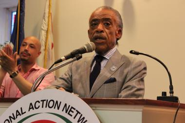 Al Sharpton addresses the crowd at a rally to save Interfaith Hospital, with Kirsten John Foy in the background.