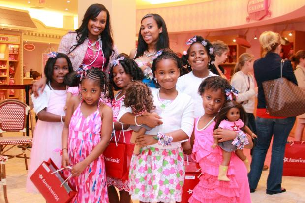 <p>Girls pose with their dolls. Teacher Rob Robinson took 27 young students of color to the American Girl store in Manhattan.</p>