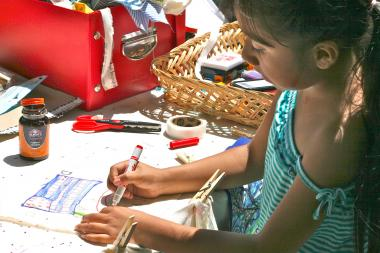 A girl works on the Prayer Flag Project which will be displayed during the Kew Gardens Community Arts Day this Sunday.