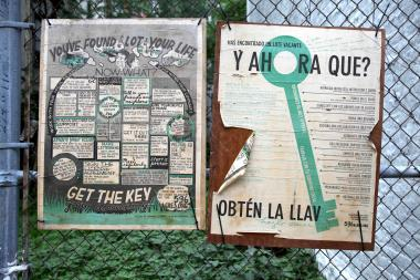 596 Acres signs for land advocacy hang over the fence of a vacant lot in Harlem.