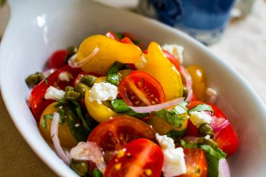 This grape tomoto salad combines the sweetness of grape tomatoes with basil, feta and a red wine vinaigrette.