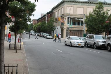 Police are looking for a man who pushed an unsuspecting 45-year-old man into traffic Tuesday morning while he was crossing 126th Street between Lenox and Fifth avenues.
