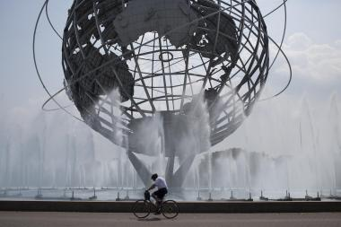 A man rides his bike past the mist from the sky-high fountains of the Unisphere in Flushing Meadows Corona Park.