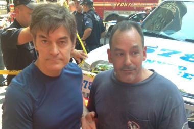 Dr. Mehmet Oz (L) poses with plumber Dave Justino after they helped save the life of British tourist Sian Green following a cab crash in Midtown on Aug. 20, 2013.