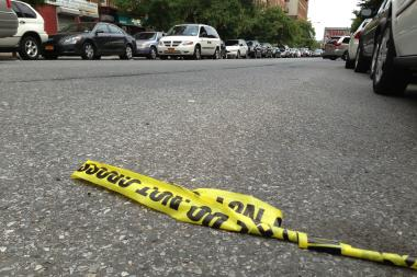 Police tape strewn in a roadway. Two men were shot on Park Ave. early Saturday, and only one survived, police said.