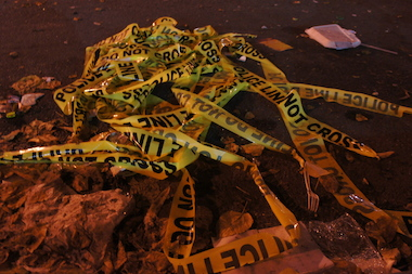 A pile of police tape on the roadway. On March 7, a man was struck and critically injured while crossing the street.