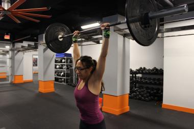 A Brick New York member lifts weight overhead.