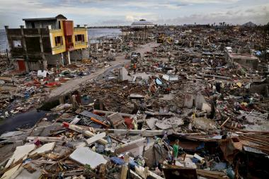 Residents search through rubble amid scenes of devastation in the aftermath of Typhoon Haiyan on November 13, 2013 in Tacloban, Leyte, Philippines.