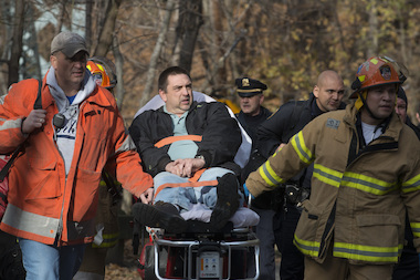 Metro-North engineer William Rockefeller is wheeled away the scene of a train derailment that killed four people and injured dozens of others.