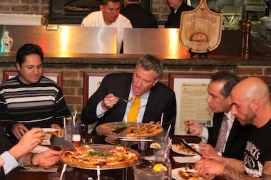 Mayor Bill de Blasio eating a slice of pizza with a fork and knife at Goodfella's on Staten Island on January 10, 2014.