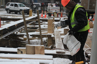 Construction works kept at their water main repair work despite the relentless snowfall.