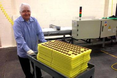 A man bringing chocolates to the foiling machine at a grand reopening celebration last October.