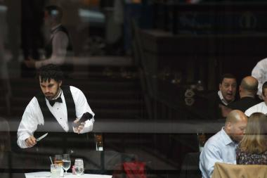 A waiter clears a table at a midtown restaurant popular for business lunches.