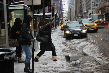 A Midtown pedestrian hops over a slushy puddle on Feb. 5, 2013.