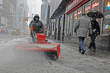 A man removes snow along Seventh Avenue in Midtown during a snowstorm on Feb. 3, 2014.