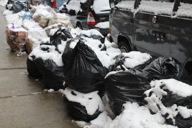 Trash bags have accumulated on city streets during the spate of snow storms.