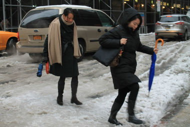 Two women try to get through the slush at the intersection of 52nd Street and 7th Avenue.