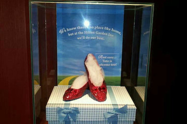 Three people were arrested for the theft of a replica pair of Ruby Red slippers from a Staten Island hotel in March, including a Washington lobbyist. The slippers were returned to the hotel with a bow missing.