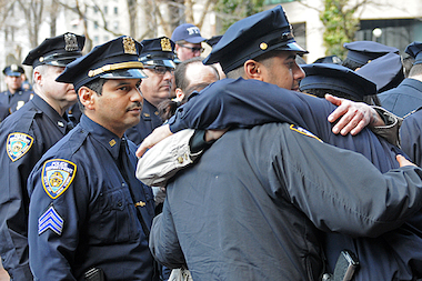 Officers embraced each other after the flag lowering ceremony to honor Police Officer Dennis Guerra, who died Wednesday of his injuries sustained during a fire over the weekend.