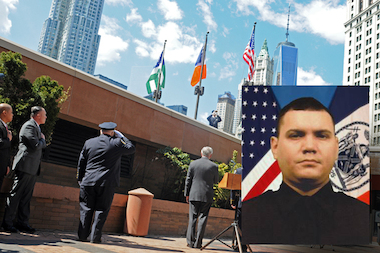 Officer Dennis Guerra, inset, was honored at a flag-lowering ceremony at NYPD headquarters after he died from injuries he sustained while responding to an arson fire Sunday.