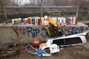 Candles and other objects form a memorial near the bank of Steinway Creek where four people were killed in a crash on April 5, 2014.