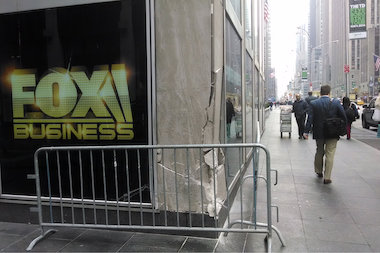 Five people were hurt when a car slammed into the News Corp. Building Monday, witnesses said.