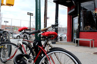 Five cycles locked to sign posts and a U-shaped bike rack in Red Hook on Van Brunt Street in front of Hope & Anchor, a neighborhood bar and restaurant.