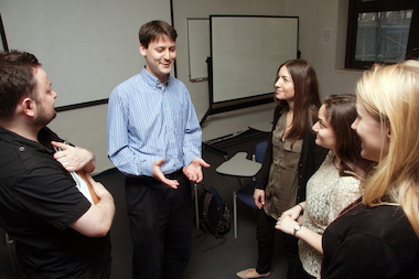 Yair Kramer, a psychologist at Brooklyn College's counseling center, talks to colleagues at the Flatbush school.