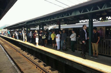 Commuters clogged platforms as the 7 train experienced delays Tuesday morning, riders said.