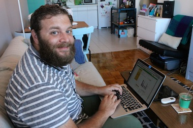 Brooklyn resident Barry Hott, 27, poses after checking out his air conditioner usage on his laptop, using a wireless system provided by Con Edison and NYC-based tech company ThinkEco.