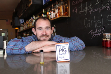 Joe Tangney, a Bushwick resident and bartender, recently launched Filthy Pig Soap. Here, he sits with bar of his soap next to the scented oil he uses to make it.