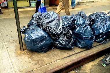 Stacked bags of garbage ooze onto a sidewalk in Chinatown.