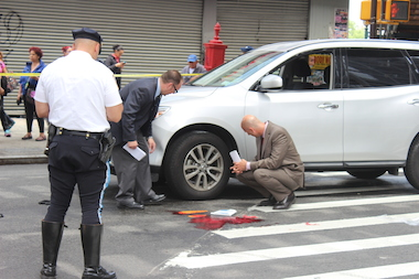 Detectives investigate the scene where a pedestrian was struck at Broadway and Flushing Avenue, on June 13, 2014.