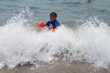 A boy plays in the waves at Rockaway Beach last July during a heat wave. Normal beach access resumes for the Fourth of July weekend after weeks of sporadic closures.