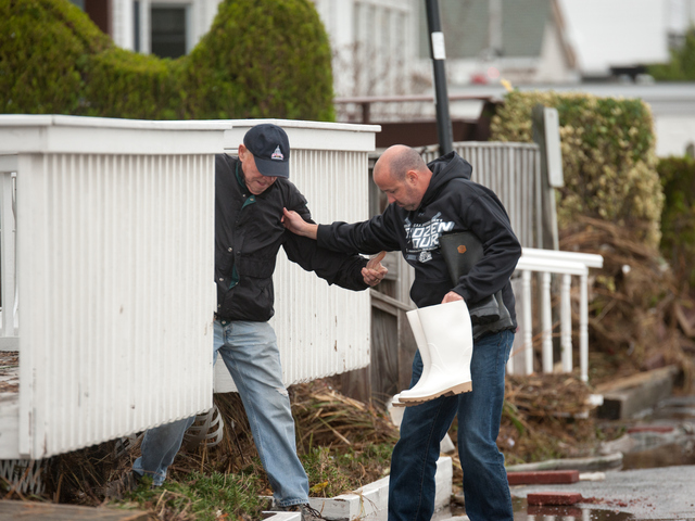<p>A man is assisted from his damaged home on Tuesday in Far Rockaway.</p>