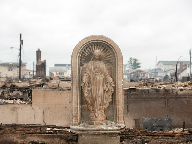 <p>A Statue of the Virgin Mary stands amidst the burnt out homes in Breezy Point on Tuesday October 30, 2012.</p>