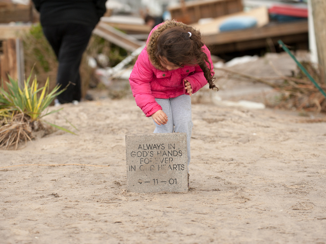 <p>Five year old Ava Reyes looks at a stone slab bearing a 911 tribute on Wednesday October 31st, 2012. This piece survived the storm and was part of a larger 911 Memorial on Stehn Promenade that was built by her grandfather.</p>