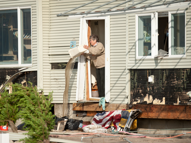 <p>A resident begins the post storm clean up on Oct. 31, 2012.</p>