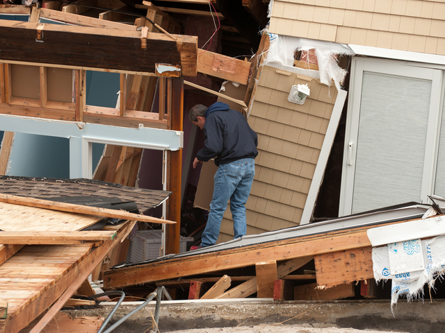 <p>A resident returns to his destroyed home on Oct. 31, 2012.</p>