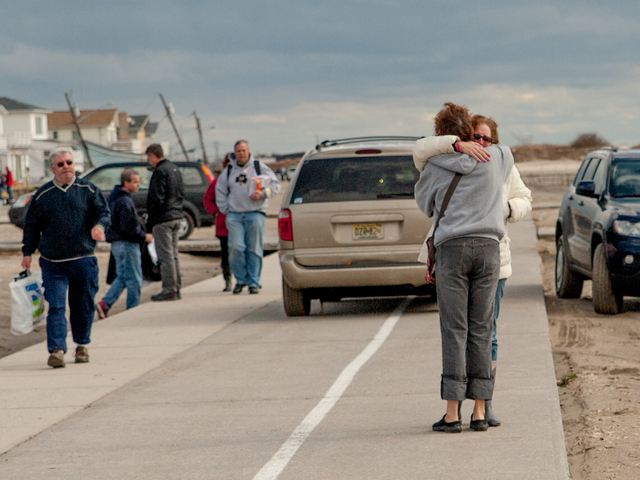 <p>Residents overcome by the devastation comfort each other in Breezy Point on Oct. 31.</p>