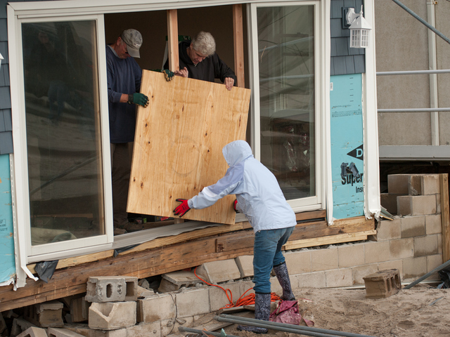 <p>Residents try to secure their damaged homes in the Rockaways just days after Hurrican Sandy ripped through the area.</p>