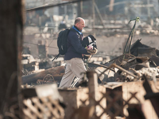 <p>A man walks through the smoldering rubble with a few of his possessions in Breezy Point on Wednesday.</p>