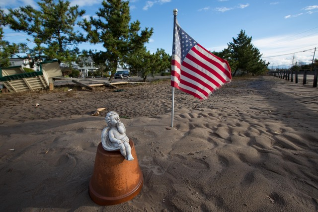 <p>A statue of an angel was set up next to the flag of America in Breezy Point.</p>