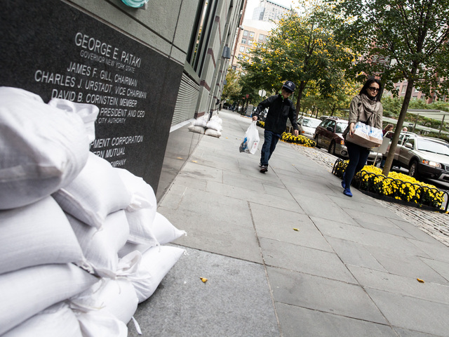 <div> 	A mother and her son carry water back to their apartment in Battery Park City in preparation for Hurricane Sandy on Oct. 28th, 2012.</div>