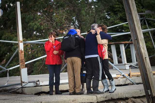 <p>Breezy Point neighbors embrace each other on October 31, 2012 after surveying the destruction caused by Hurricane Sandy.</p>