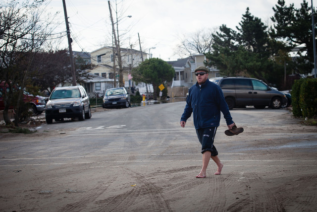 <p>Residents walked with bare feet to cross water in the devastated area of Breezy Point on October 31, 2012.</p>