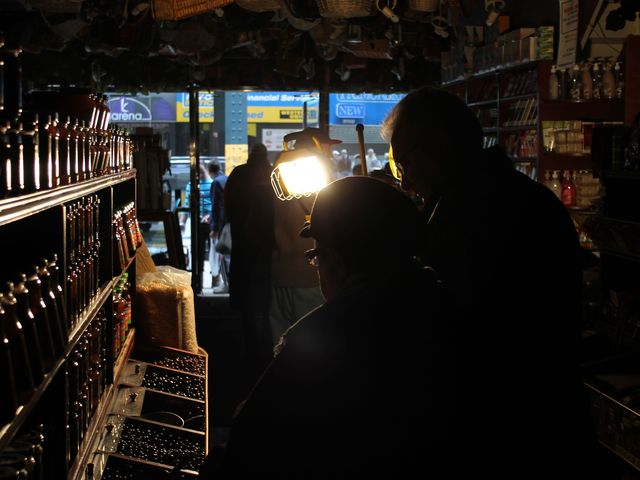 <p>Customers browse in Brooklyn&#39;s Gourmet Specialty Goods, which was lit only by generator-powered floodlights.</p>