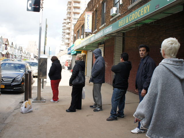 <p>Residents line up to use a payphone in Brighton Beach. The neighborhood&#39;s stores were open and its streets were crowded Wednesday despite flooding and continued blackouts.</p>