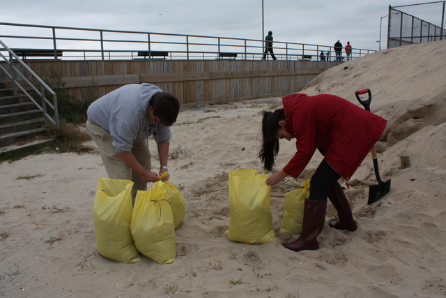 <p>Brendan and Bianca Brosh pack bags full of sand at Rockaway Beach for securing their home during Hurricane Sandy, on October 28, 2012.</p>